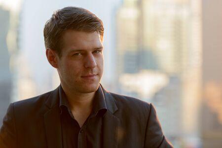 Photo pour Face of young handsome businessman against view of the city - image libre de droit