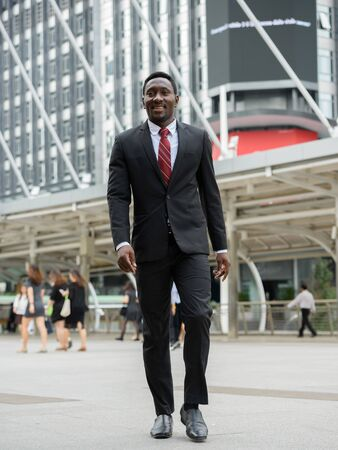 Photo pour Happy young handsome African businessman walking in the city outdoors - image libre de droit
