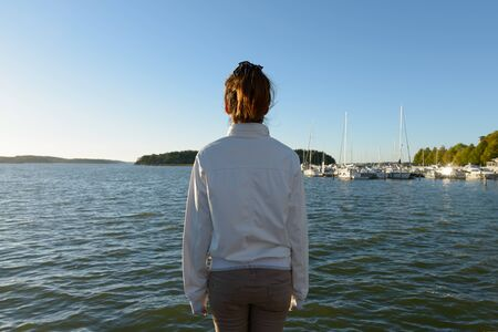 Photo pour Rear view of young Asian woman looking at view of the sea - image libre de droit