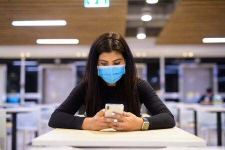Photo pour Young Indian woman with mask using phone and sitting with distance at food court - image libre de droit