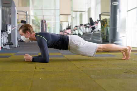 Photo pour Full body shot of young man with mask doing plank position on the floor at gym during corona virus covid-19 - image libre de droit