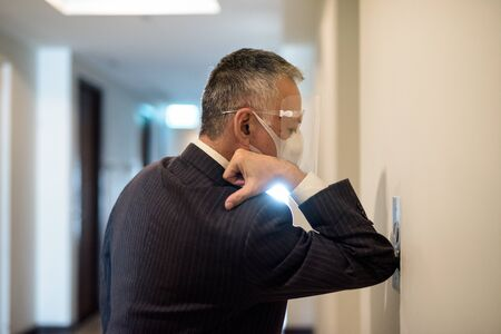 Photo pour Mature Japanese businessman with mask and face shield pressing elevator button with elbow - image libre de droit