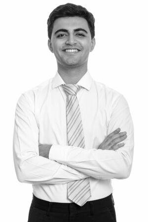 Photo pour Portrait of happy young handsome Persian businessman smiling with arms crossed - image libre de droit