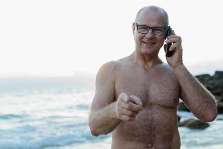 Photo pour Mature handsome tourist man shirtless at the beach - image libre de droit