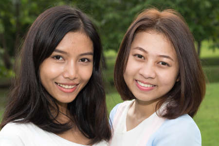 Photo for Portrait of two young Asian teenage girls as friends together at the park - Royalty Free Image