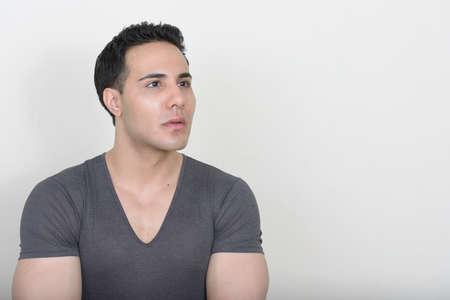 Photo pour Portrait of young handsome man against white background - image libre de droit
