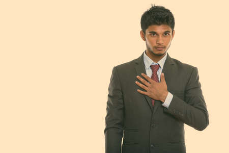 Photo for Studio shot of young handsome Indian businessman with hand on chest - Royalty Free Image
