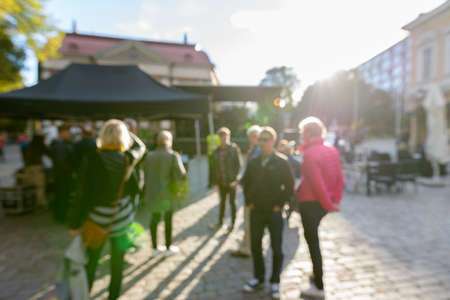 Photo pour Defocused crowd of people looking busy in front of black canopies in the street on sunny day - image libre de droit