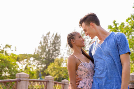 Photo for Portrait of young multi ethnic couple relaxing together at the park - Royalty Free Image