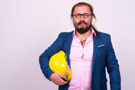 Photo pour Bearded businessman with hardhat against white background - image libre de droit