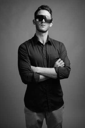Photo pour Portrait of young handsome businessman against gray background - image libre de droit