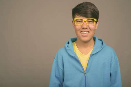 Photo pour Young Asian teenage boy against gray background - image libre de droit