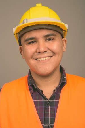 Photo pour Young Asian man construction worker against gray background - image libre de droit