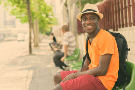 Photo pour Young happy black African tourist man smiling and thinking while sitting at the bus stop in the streets of Bangkok Thailand - image libre de droit