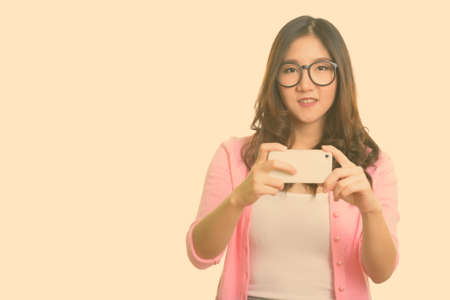 Photo for Young happy Asian woman taking picture with mobile phone - Royalty Free Image