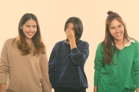 Photo pour Studio shot of three happy young Asian woman friends smiling and laughing together - image libre de droit