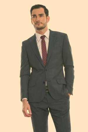 Photo pour Studio shot of young handsome businessman standing while thinking with hand on pocket - image libre de droit