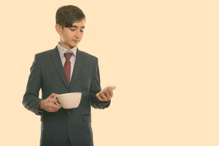 Photo for Studio shot of young handsome Persian teenage businessman holding coffee cup and using mobile phone - Royalty Free Image