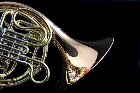 A brass and copper French horn isolated against a black background in the horizontal format with copy space.