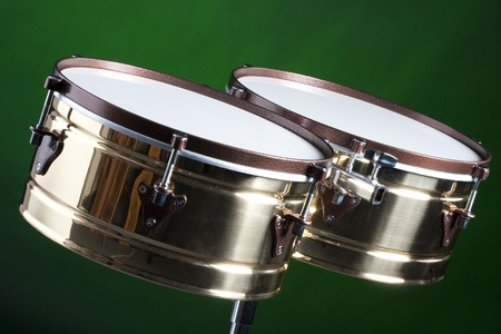 A set of brass and copper timbales isolated on a green background in the horizontal format.