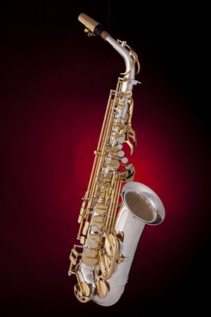 A professional saxophone isolated against a red spotlight background in the vertical format.