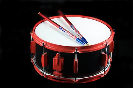 A red trimmed black snare drum and flag colored sticks isolated on black background in the horizontal format with copy space.