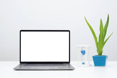 Photo for Mock up laptop with blank screen and plant with sandglass for display banner or advertise. - Royalty Free Image