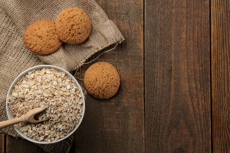 Photo pour Dry oatmeal and oatmeal cookies in a white bowl and a wooden spoon. food. healthy food. on a brown wooden table. top view with space for inscription - image libre de droit