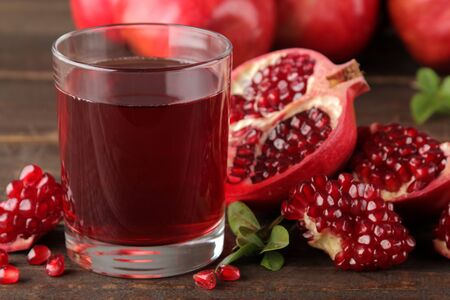 Photo pour Pomegranate juice in a glass with fresh pomegranates around on a brown wooden table - image libre de droit