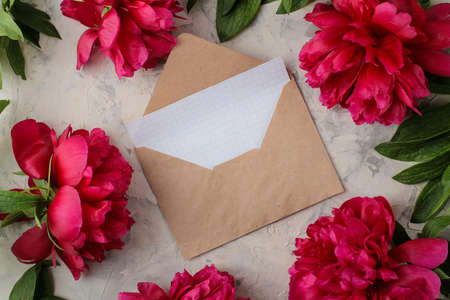 Photo pour Beautiful bright pink flowers peonies and an envelope with a blank and on a bright concrete background. top view. space for text - image libre de droit