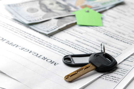 Photo pour mortgage application. Key with house key fob and blank and money on a brown wooden table. concept of buying a home. - image libre de droit