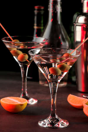 Photo pour Martini. Alcoholic drink martini with olives in a glass on a dark background in the bar on the bar counter. bar inventory. cocktails - image libre de droit