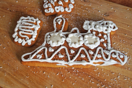 Christmas gingerbread decorated with white icing lie on a wooden table