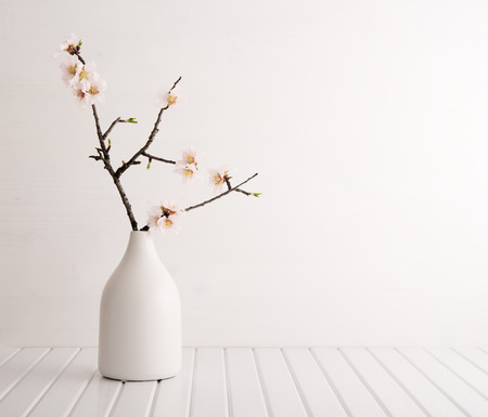 Vase with cherry blossom on wooden background