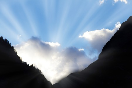 sun bursts through clouds from a dark mountain valley symbol for hope,call not to give up,light at the end of the tunnel