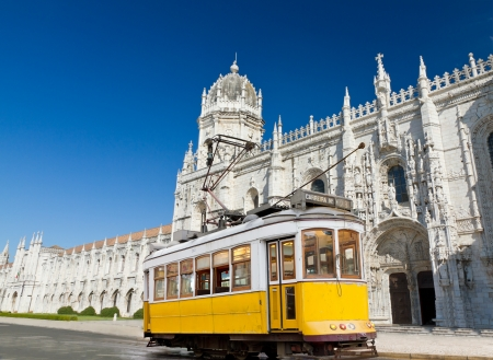 historic classic yellow tram of Lisbon built partially of wood in front of famous Jeronimos monastery, Portugal
