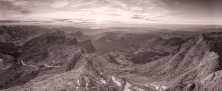 black and white panorama of high alpine ragged sharp karst mountain top ranges disapear in misty distance at sunset, Switzerland
