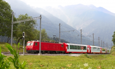 Glacier express train passes high mountain valley, Switzerland