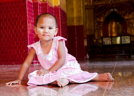 young burrmese girl dressed up nicely for temple visit with make up called thanaka ear rings, neclace and pink dress, Burma