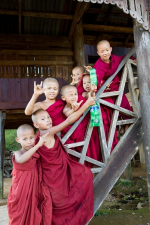 HPA AN, BURMA-OCT.  30: A group of young buddhist monk boys poses wearing maroon cowls at old monastery on October 30, 2011 in Hpa An, Burma.