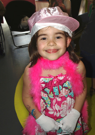 Smiling young girl looking at viewer playing dressup