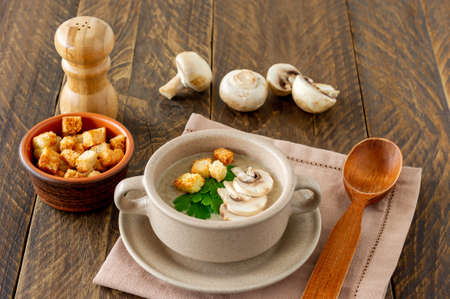 Photo pour Mushroom cream soup with champignons, croutons and fresh herbs on rustic white wooden table. - image libre de droit