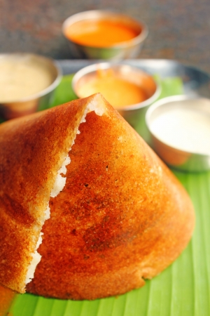 Masala Dosa - Closeup macro photo one of the most popular south indian breakfast served with different types of chutney, sambar and ghee.