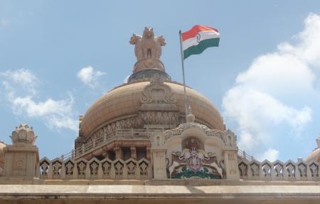 Indian national flag in tri color (orange, white & green) with ashoka chakra on vidhana soudha legislative building at bangalore, karnataka with dome &  national emblem of india(lions) in background