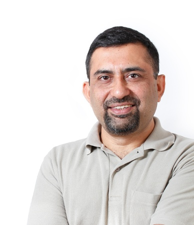 Handsome and happy middle aged mature indian adult business man looking with satisfaction and happiness  The person is wearing t-shirt and  is shot in studio with white background