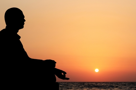 A young man sitting in lotus position and meditating on a beach in the evening with sun setting in the background. The sky is orange yellow and the ocean can also be seen in the meditation backdrop