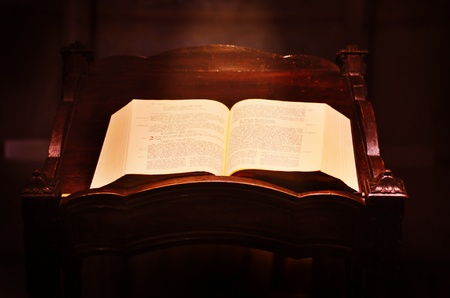 Opened old Bible with light beam galling on it in the church