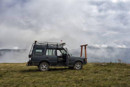 Photo pour SUV car on a mountain top with clouds around. - image libre de droit