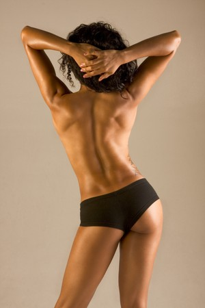 Very fit, muscular athletically built topless woman standing with her back towards to camera
