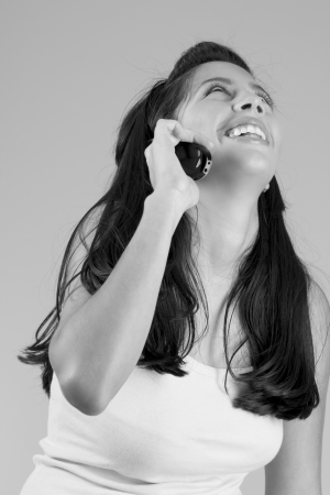 Happy  Hispanic girl talking on cell-phone